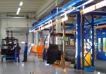 Overhead monorail system with painting cabin for the transport of components for the utility vehicle manufacturing